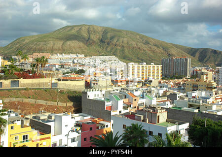 Small town and tourist resort in south-west coast of the island, in Arona Municipality with Montana de Guaza in the background, Los Cristianos, Spain - Stock Image