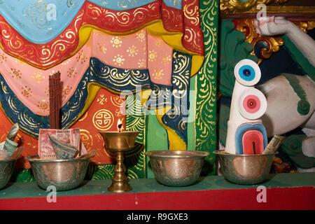 Nepal, Everest Base Camp Trek, Khumjung, Samten Choling Gompa interior, butter sculpture, lamps and donations on altar - Stock Image