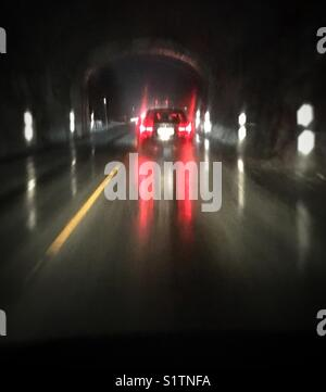 Car driving on a very wet road out of a tunnel. - Stock Image
