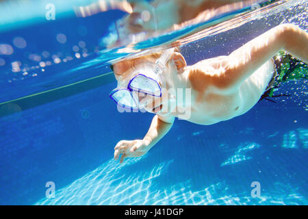 Child swims underwater in swimming pool with snorkel mask - Stock Image