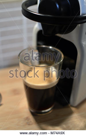 Closeup of home 'pod' style coffee maker with tall glass containing black coffee on wooden table in kitchen. - Stock Image