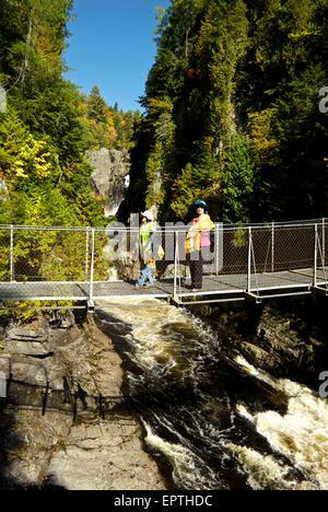 Asian visitors crossing Canyon Ste Anne River pedestrian suspension bridge - Stock Image