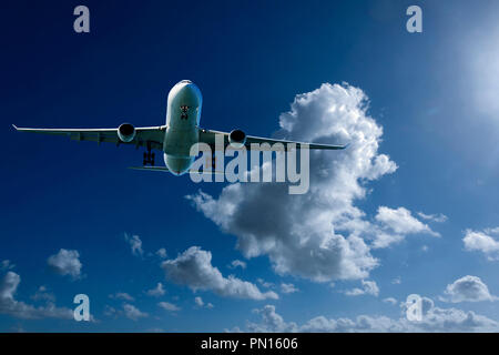 An artistic skyscape view of a commercial passenger jet aircraft flying in a vibrant blue sky, with bright white coloured billowing Cumulonimbus clouds - Stock Image