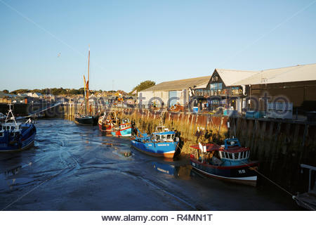 Fishing boats moored at Whitstable harbour in front of fish market; Whitstable, Kent. - Stock Image