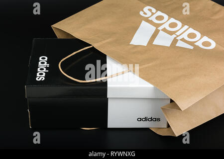 BURGAS, BULGARIA - MARCH 8, 2019: Paper bag with original Adidas logo and Adidas shoes box on black background. - Stock Image