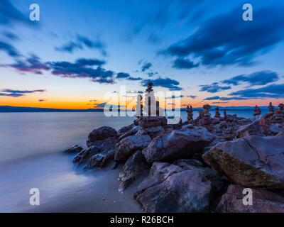 Stack of rocks on beach arty rendition in late evening dusk time blurry clouds due to creative long exposure - Stock Image