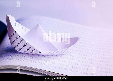 Paper boat sails on open book - Stock Image