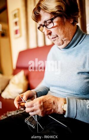 Senior knitting a stocking on the sofa at home, North Rhine-Westphalia, Germany - Stock Image