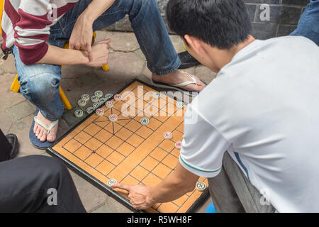 2 men, on the street in Hanoi, Vietnam, play Xiangqi, popular in Asia board game, known also as chinese chess. - Stock Image