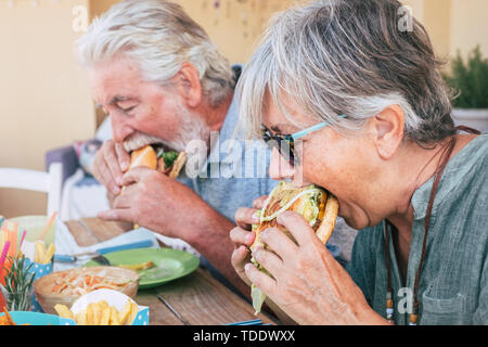 People eating hamburger junk food - Couple of senior man and woman with fast food lunch time - close up of elderly no healthy lifestyle - tasty sandwi - Stock Image