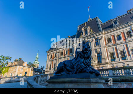 Statue of a lion in front of the Pszczyna Castle - classical-style palace. Pszczyna, Poland. - Stock Image