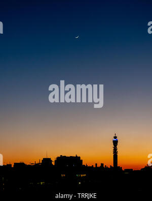 London, England, UK - March 7, 2011: A crescent moon hangs over the cityscape of London, including the BT Tower, silhouetted against the sunset. - Stock Image