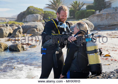 Dive instructor checking equipment of training diver - Stock Image