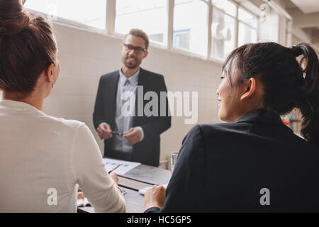 Two young woman sitting in a meeting in office, with businessman standing in background. Business presentation in - Stock Image