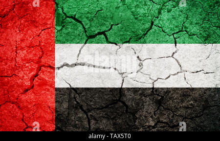 United Arab Emirates flag on dry earth ground texture background - Stock Image