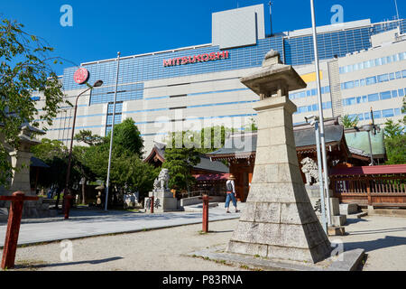 Low angle shot of Japanese lanterns in Kego Shrine with modern shop buildings in the background. In Tenjin, central Fukuoka, Japan - Stock Image