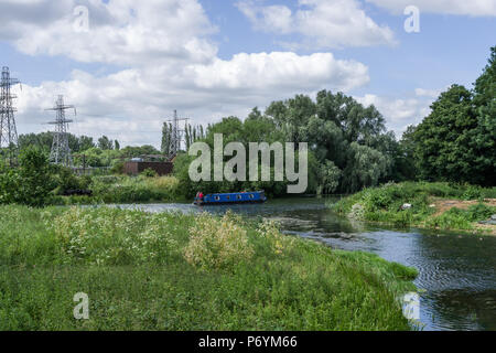 The River Nene flowing through Midsummer Meadow, Northampton, UK; with a blue narrowboat in the middle distance. - Stock Image