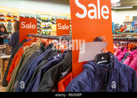 Sale signs on racks of clothes in a shop, UK - Stock Image