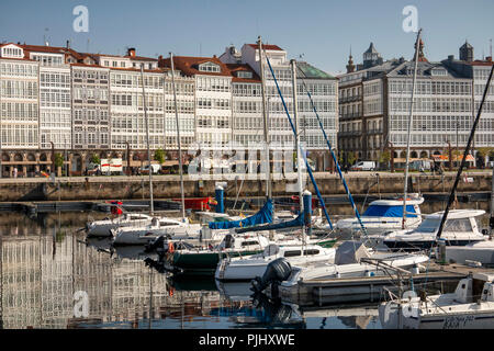 Spain, Galicia, A Coruna, harbour, boats moored in marina by glazed waterfront buildings - Stock Image