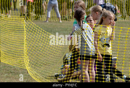 Some young girls behind a yellow plastic mesh fence waiting for an obstacle course race to pass - Stock Image