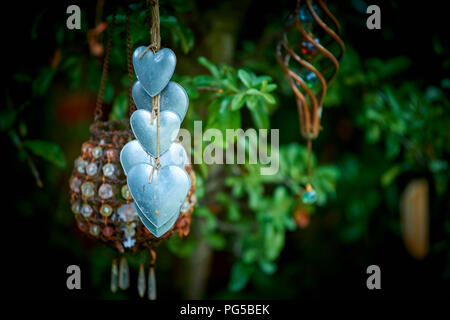 Hanging heart shaped ornaments in a pretty garden - Stock Image