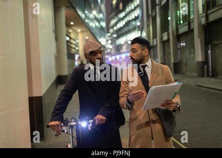 Businessmen with bicycle and paperwork walking on urban sidewalk - Stock Image