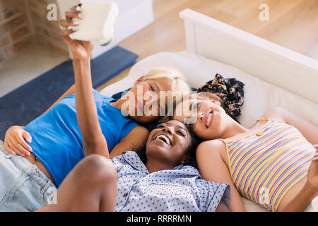 Young women friends using instant camera on bed - Stock Image
