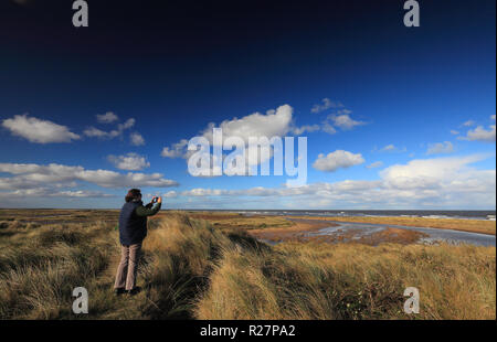 Woman taking a photo of the scene at Holme Next The Sea Dunes Nature Reserve. - Stock Image