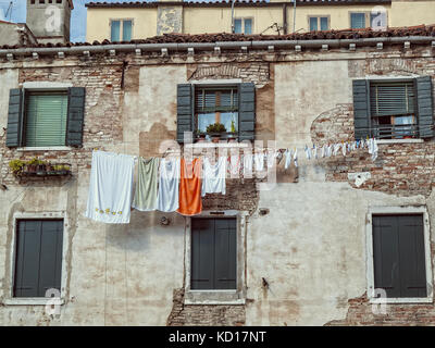 Washing hanging on a line on an old building next to a canal near the Arsenale in Venice - Stock Image