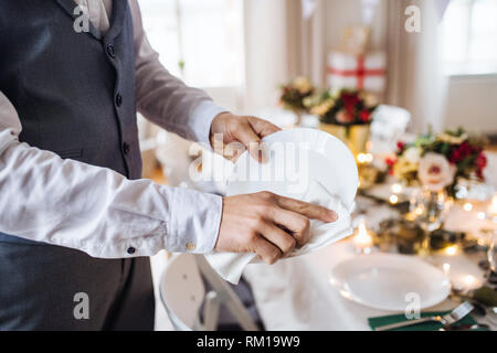 A midsection of man indoors in a room set for a party, polishing plates. - Stock Image