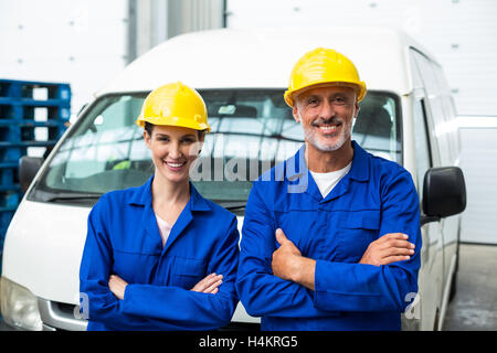 Portrait of warehouse workers standing together with arms crossed - Stock Image