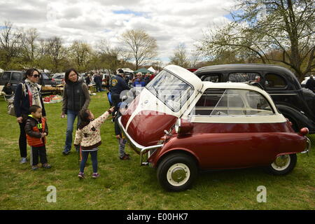 Floral Park, New York, U.S. 27th April, 2014. Family with young children look at the 1958 BMW Isetta 300 at the 35th Annual Antique Auto Show at Queens Farm. Designed by the Italian refrigerator company ISO, it has a refrigerator-like front door which swings open to let the driver and passenger enter. Credit:  Ann E Parry/Alamy Live News - Stock Image