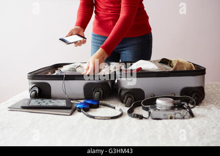 Woman packing suitcase, holding smartphone, mid section - Stock Image