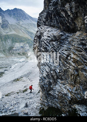 Hiker moving across rocky terrain, Mont Cervin, Matterhorn, Valais, Switzerland - Stock Image