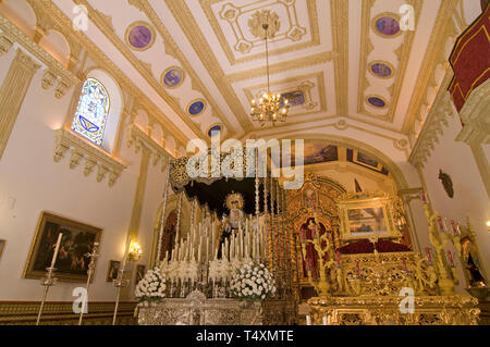 Holy Week. Hermitage of Our Lady of Solitude (interior with 'pasos' (platforms with religious statues). Hinojos. Huelva province. Region of Andalusia. - Stock Image