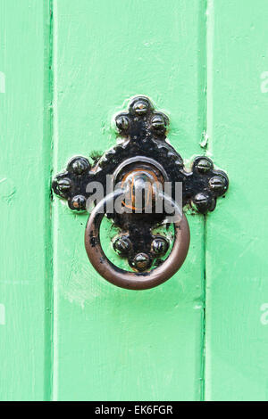 A black metal knocker on a green wooden door - Stock Image