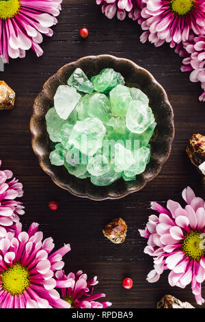 Flourite Crystals with Garnet and Pink Mums on Dark Wood - Stock Image