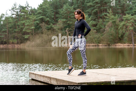woman runner resting with a sports bottle of water beside a lake - Stock Image