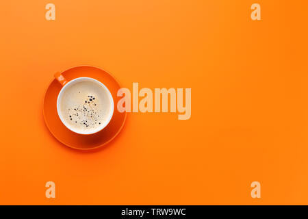 Orange coffee cup over orange background. Top view flat lay with copy space - Stock Image