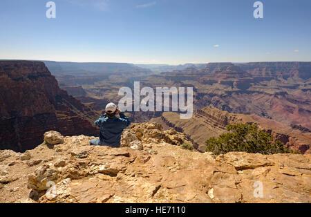 Adventure travel man at edge of the Grand Canyon south rim Pipe Creek Vista taking photo, Arizona USA rear view - Stock Image
