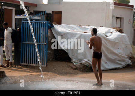An Indian man takes a shower outside his house. Rajasthan, India. - Stock Image