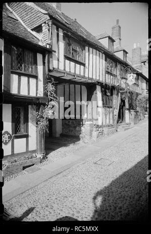 Mermaid Hotel, Rye, Rother, East Sussex, c1955-c1980. The south elevation of the Mermaid Hotel, a 15th century timber framed building with an interior courtyard, seen from the south-east on Mermaid Street. The image shows the whole of the south elevation, which has two storeys, attics and a five-window range on the first floor, and a wide entrance to the courtyard in the foreground. Beyond a window is the entrance with three steps from the cobbled street, and a sign overhead with a relief of a mermaid. The hotel carries on into a further building on the other side of the courtyard to the north - Stock Image