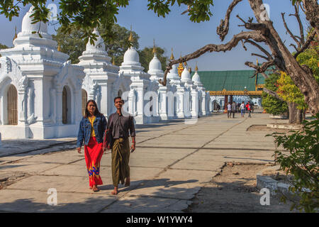 A young couple walking inside the Kuthodaw pagoda in Mandalay - Stock Image