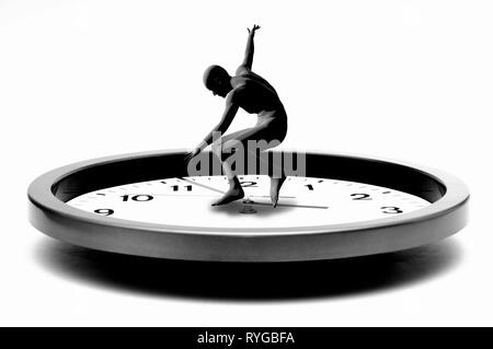 model of a humanoid figure in a dancing pose on a clock, concept for time and youth passing by - Stock Image