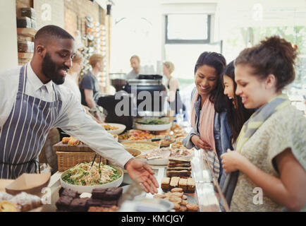 Male worker helping female customers in cafe - Stock Image