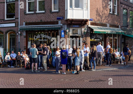 Young people drinking outside Café Heuvel in Amsterdam, Netherlands - Stock Image