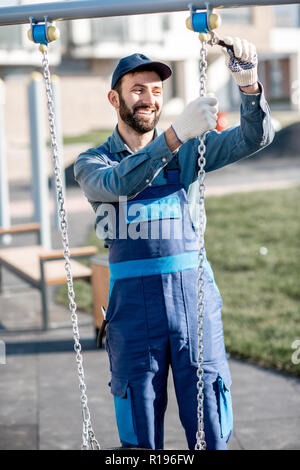 Handsome workman in uniform mounting swing on the playground outdoors - Stock Image