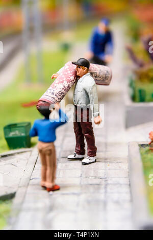 Miniature model of a man carrying a rolled up rug, at Kolejkowo, Wrocław, Wroclaw, Wroklaw, Poland - Stock Image