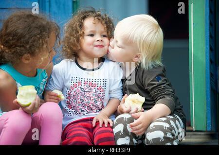 Boy kissing girl on cheek - Stock Image