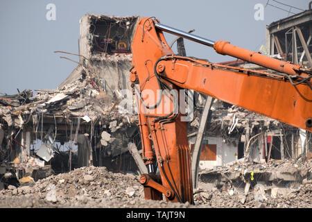 Big demolition machine demolishing a factory - Stock Image